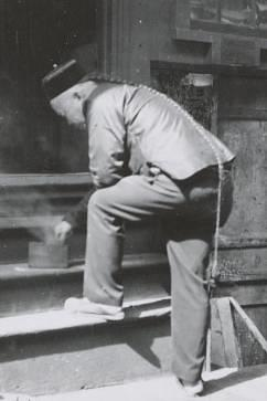 A black-and-white photograph from three-quarter back view of a man wearing a round cap and a long braided queue that reaches to the back of his right knee. His left foot is posed on the first step of a four-step wooden staircase. Bending forward to touch a cylindrical container from which smoke is rising, ahe is resting his left elbow on his folded left knee.