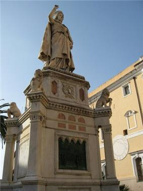 Oristano: Statue of Eleanor of Arborea, holding the Carta de Logu in her hand, with the sundial on the wall of the City Hall in the backdrop.