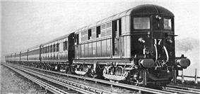 A black and white image of an electric locomotive hauling at least 6 coaches, shown with the electric locomotive on the right. A track in the foreground is electrified with the fourth rail system. The locomotive is shown with two pick-up shoes.