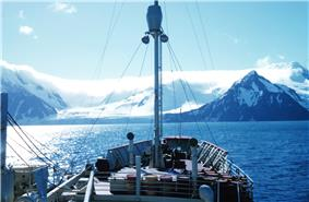On-board view towards the bow of a small boat with a mast. Beyond the bow is a shoreline of snowy mountains.