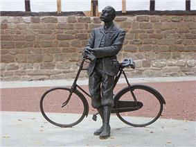 Modern statue of man with moustache in Edwardian cycling clothes holding the handlebar of an ordinary bicycle
