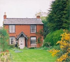 a brick country cottage with a large front garden