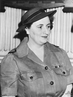 Black-and-white photograph of a dark-haired woman in a military uniform and wearing a hat