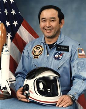 An image of LTC Onizuka with a model of the Challenger shuttle and astronaut helmet on a desk in front of him. The United States Flag, and a smoky blue backdrop in the background.