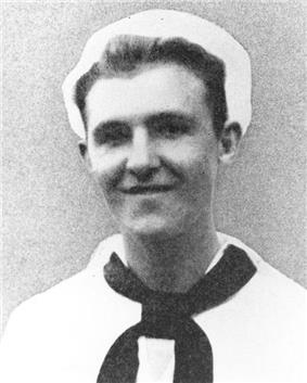 Head and shoulders of a smiling young white man wearing a naval uniform consisting of a white shirt with a dark scarf tied around the neck and running under the large, flat, collar, and a white