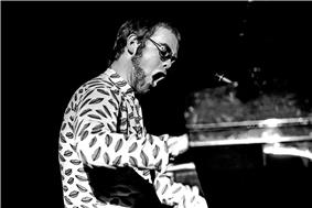 A black and white photo of Elton John in an elaborate glam costume, playing the piano.