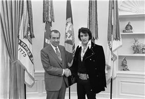 A mutton-chopped Presley, wearing a long velour jacket and a giant buckle like that of a boxing championship belt, shakes hands with a balding man wearing a suit and tie. They are facing camera and smiling. Five flags hang from poles directly behind them.
