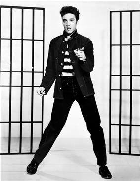 A black and white photograph of Elvis Presley standing between two sets of bars