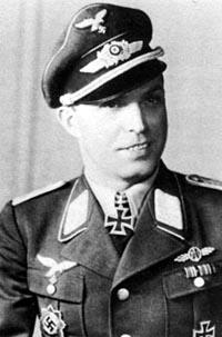 The up body of a man, shown from the front. He wears a peaked cap and a military uniform with various military decorations and an Iron Cross displayed at the front of his shirt collar. He is smiling; his eyes are looking to the left of the camera.