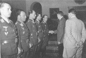 Five men all wearing military uniforms and decorations standing in row. The man on the far right is shaking hands with another man whose back is facing the camera. Another man is standing behind the men shaking hands.