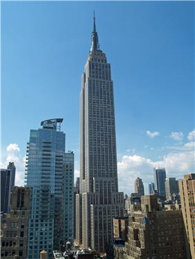 Aerial view of a 100-story building with several setbacks; the building tapers into a large circular spire near its 90th floor and is topped by a large antenna.