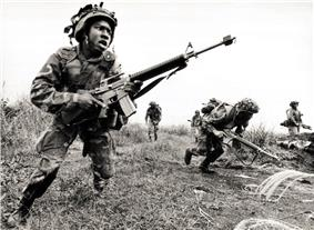 Two Marines with blank firing adaptors on their rifles assault through a field while others watch.