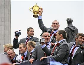 White men in grey suits, pale blue shirts and red ties celebrate upon the top floor of an open-top bus. On man holds a golden trophy in the air with one hand.