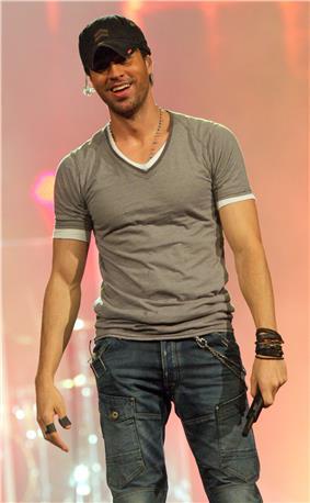 Enrique Iglesias, facing front, holding a microphone.