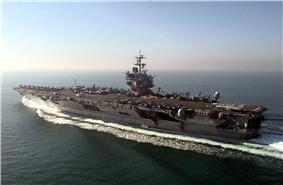 Aircraft carrier steaming away from camera in open sea. On deck is a large contingent of aircraft