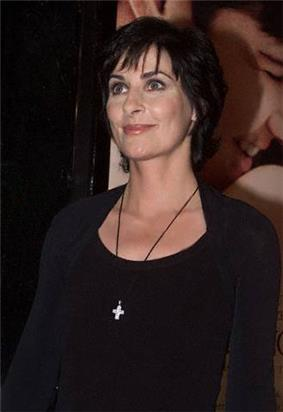 A woman in black clothing, wearing a necklace with a cross-shaped jewel