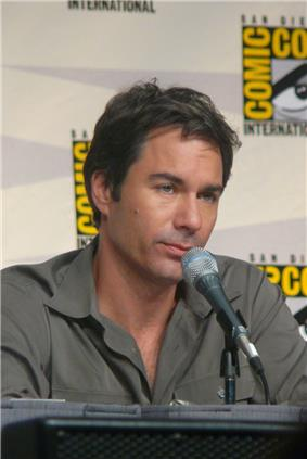 A caucasian male with dark hair wearing a grey shirt is facing to the right, a microphone is in front of him.