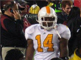 An American football player is seen in full orange and white gear wearing the number 14.