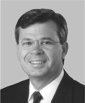 A dark-haired man in his forties wearing glasses and a suit. He is smiling and facing left.