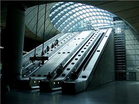 View of escalators rising up from the darkness of the station concourse to the brightness of the arched glazed roof over the entrance