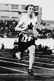 A woman sprints down a track during a race. She has short hair and is wearing dark shorts and a white shirt with a stylized maple leaf logo over the word