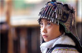 An ethnic Hani girl with a typical Hani headgear for children. Near Yuanyang, Yunnan Province, China
