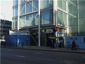 A building covered in windows with a blue sign reading