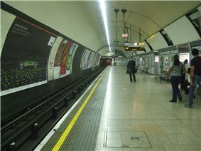 A wide concrete platform in a circular tunnel. Railway track runs along the left with posters fixed to the wall opposite the platform.