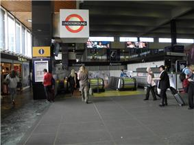 Passengers cross a paved concourse towards escalators that head down into the station entrance. A large