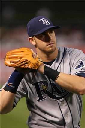 A man in a gray and blue baseball uniform with the letters