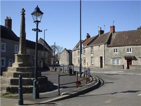 Street scene. Stone cross on a pillar rising from 5 step plinth. Iron lampost left and right of the road are stone terraced houses.