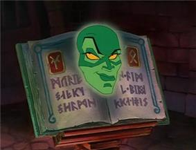 A green face, resembling that of a woman, is resting upon a book; the pages on either side are marked with Runic-like inscriptions. A cunning smile runs across her face, and her yellow eyes are looking upward.