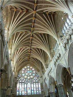 The interior of the nave at Exeter shows a great richness and diversity of decoration. Above the Gothic arcade runs an ornately sculptured blind gallery, above which rise clerestory windows full of Geometri tracery. The wide western window of nine lights beneath an upper rose fills the western end. The vault has many ribs of strong profile, which spring out in clusters like palm branches.