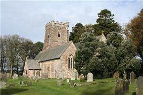 Stone building with square tower. Trees are to the right and behind with gravestones in the foreground.