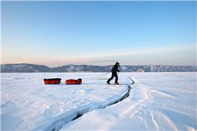 A man pulling two sledges on a frozen lake, approaching a crack in the ice