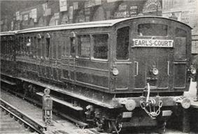 A three-quarter black-and-white photograph of a train standing at a station, showing the end carriage with windows at the end