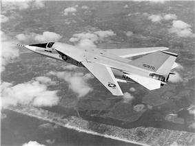 Black-and-white photo of jet aircraft flying above scattered clouds with wings swept back.