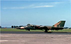 Jet aircraft parked on ramp perpendicular to camera facing left. It wears a green and brown camouflage scheme.