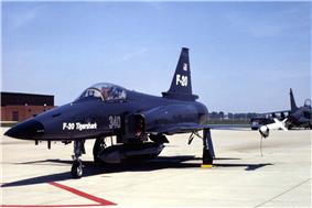 Dark-blue jet aircraft taxiing on ramp, carrying an external fuel tank under belly.