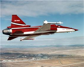 Starboard view of red and white single-engine jet fighter aircraft banking left. At the wingtips are missiles.
