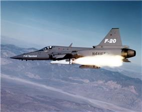 Gray jet fighter aircraft fires a white missile.