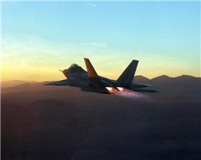 Rear view of jet aircraft in-flight at dawn/dusk above mountains. Its engines are in full afterburner, evident through the presence of shock diamonds.