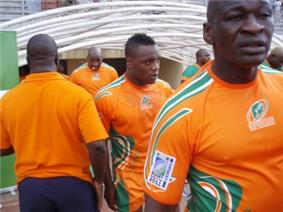 A close up shot of the Ivory Coast players, in their country's orange jerseys, entering the field from the dressing room tunnel.