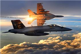 Two jet aircraft flying over clouds during dawn/dusk. The one in the foreground is perpendicular to the camera; the second further away is banking left while releasing orange flares