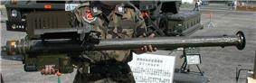 A large pipe-like weapon with a box on its lower lift hand side and upper left hand side, held up for display to the camera. A sign written in Japanese and a military truck can be seen in the background.