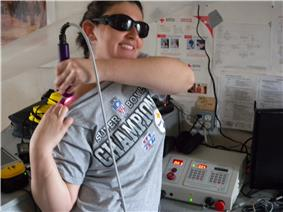 Crew member Kristine Ferrone operates a Class IV High Power Laser therapy device.