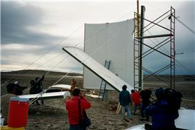 Volunteers use a scaffold to erect the walls of the station on July 21, 2000.
