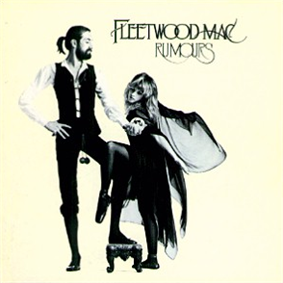 Mostly cream album cover with black-and-white image of tall, bearded gentleman holding the hand of blonde, cape-wearing woman. In the top right-hand corner, it is captioned