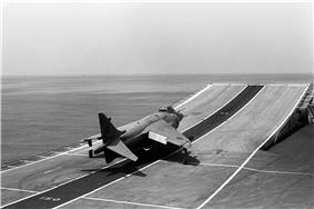 Black-and-white photograph of jet aircraft making a takeoff run at sea, approaching a ski-jump, which is a curved surface assisting aircraft in taking off