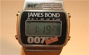 An oblong-shaped digital watch. Above the face is the name